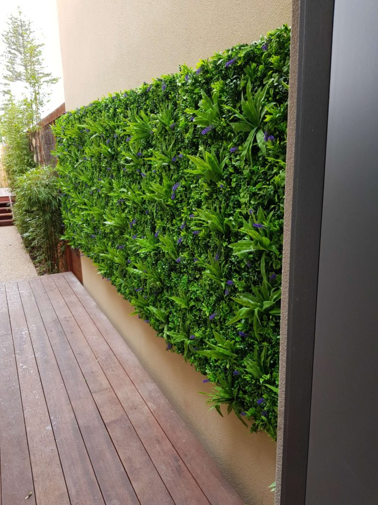 Artificial green wall near a kitchen with fake green walls