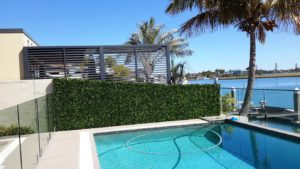 Pool side area brick wall brisbane with artificial mixed ivy panels of fake hedge panels