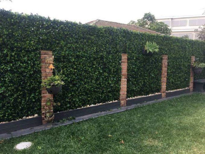 Artificial spring sensation hedge on a backyard fence for privacy