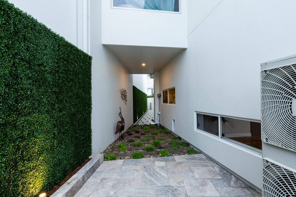 Artificial boxwood panels along a side wall