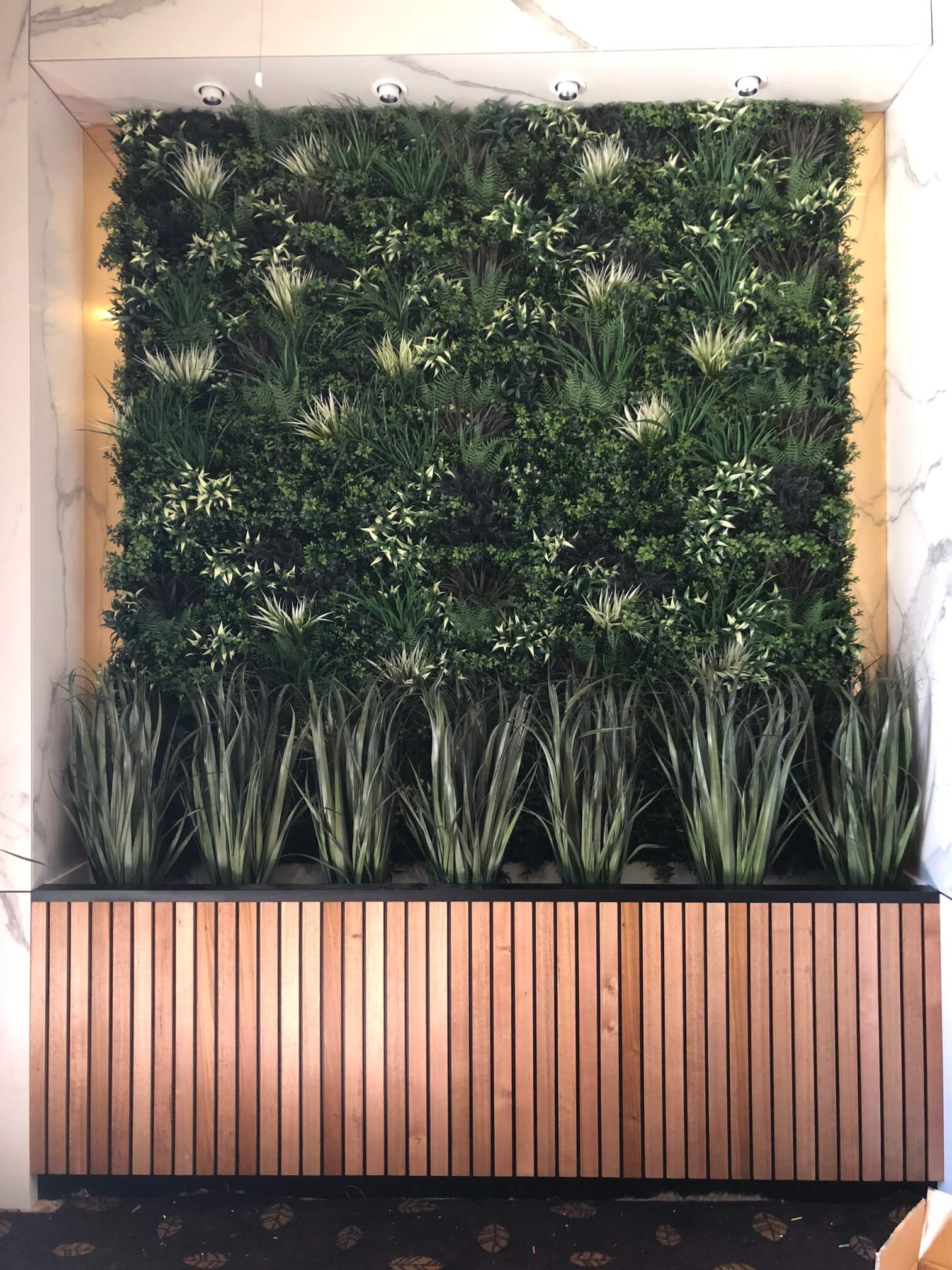 Hotel fitout with a green wall and artificial grasses in a room divider