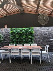 Outdoor dining area for a cafe / restaurant with a fake fern green wall