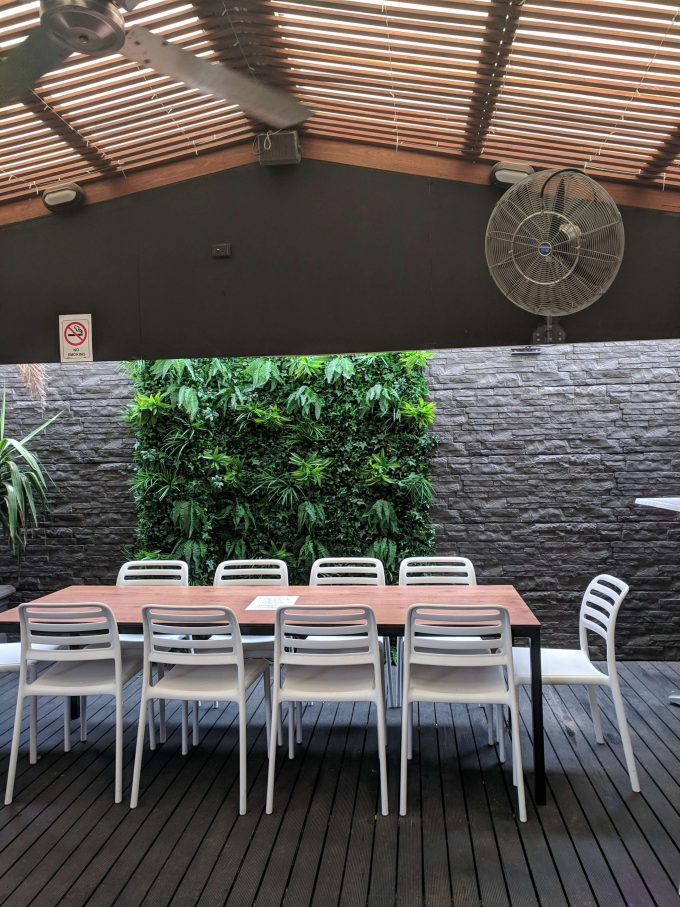 Outdoor cafe and seating area with green tropics on the wall