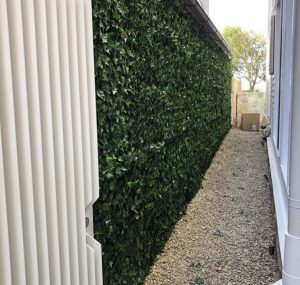artificial ivy hedge panels installed along a driveway