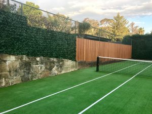 During installation a tennis court has artificial hedging attached to the fence
