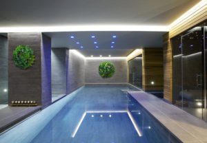 Hotel pool area decorated with fake green walls
