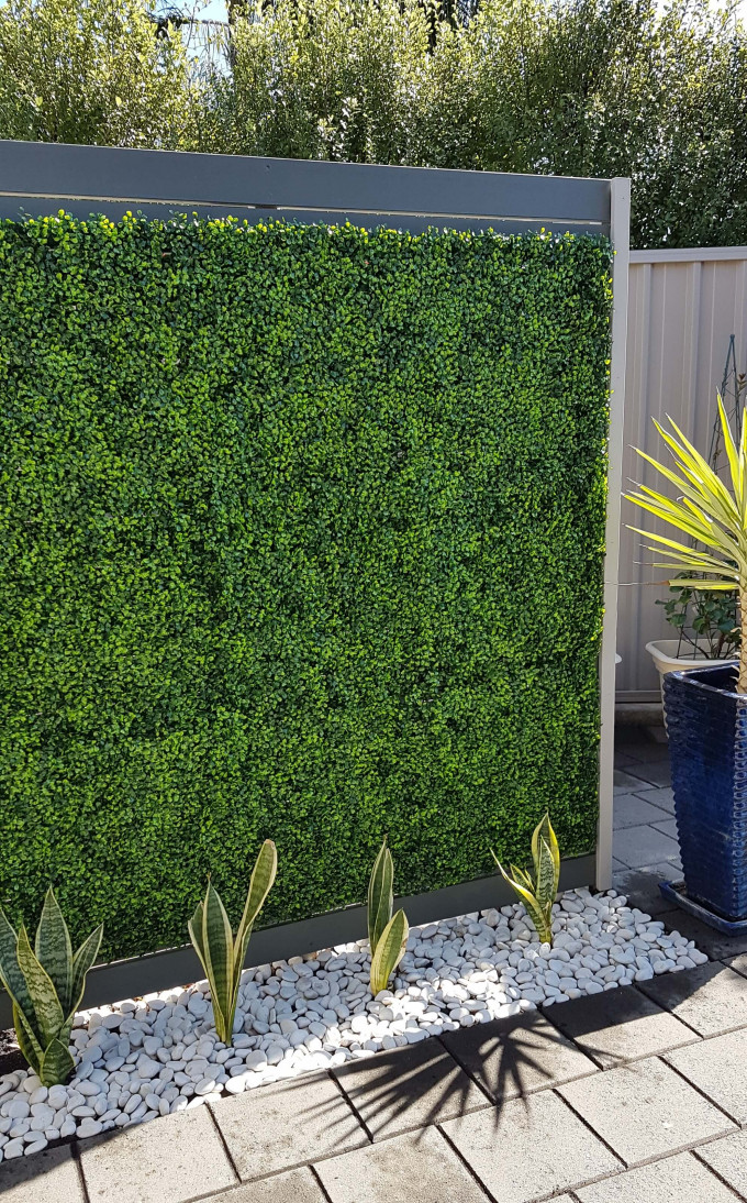 fake boxwood hedge panels on a wall