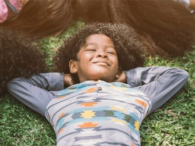 Pros and cons of real natural grass - child laying on grass