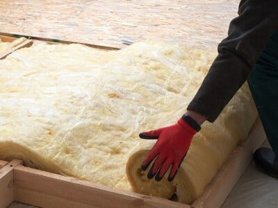 A person rolling out insulation in a home roof