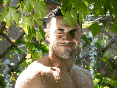 A fit man naked in his garden celebrating World Naked Gardening Day by having an outside shower with his hose