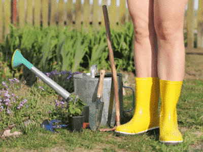 A lady naked in her garden for World Naked Gardening Day in yellow gum boots