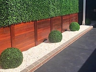 Topiary balls installed upon white pebbles add a designer look to this project