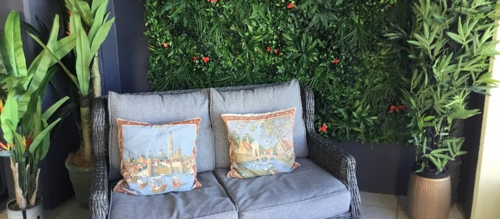 A gray outdoor sofa is flanked by artificial potted plants. In the background is an artificial vertical garden green wall