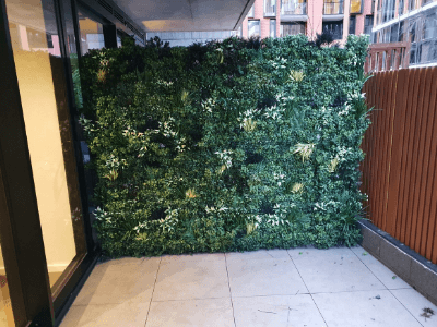 Add greenery and privacy with artificial plants and vertical gardens.